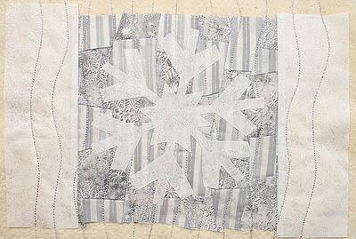 A silver, white and grey snowflake mug rug
