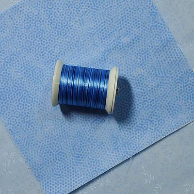 A blue spool of thread on blue fabrics