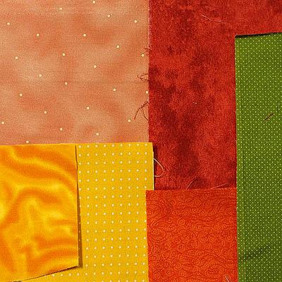 A variety of orange, yellow & green fabrics