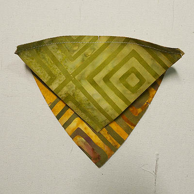 Small triangle sewn to large triangle on a curve