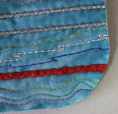 Teal fabric with a variety of stitching and couching